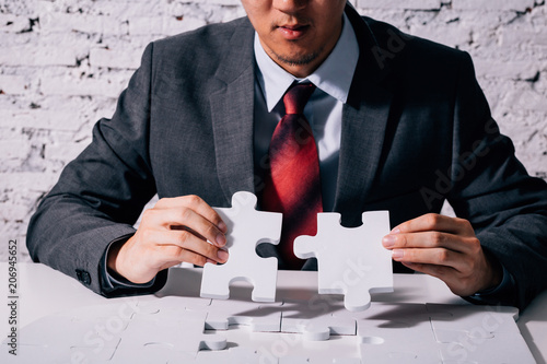 Cuadros en Lienzo Hands of business man working on finishing last missing pieces of jigsaw on the
