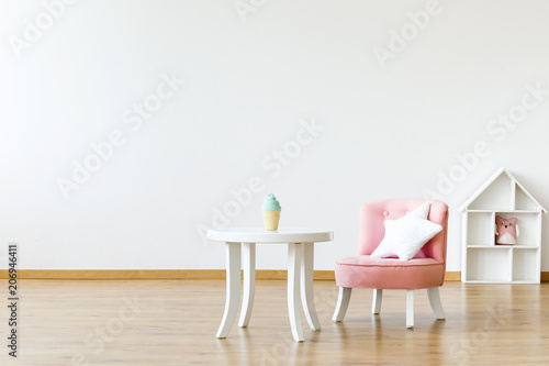 Kid's table and chair with a star pillow in a white, empty room interior with a dollhouse in the background Wallpaper Mural