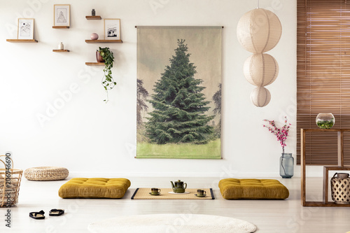 Fotografia  Japanese dining room interior with a tree poster, lamp, pillows and tatami mat w