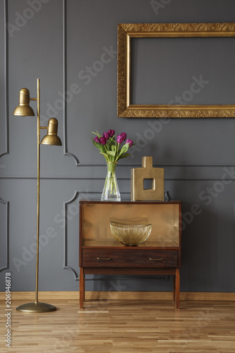Wooden Cabinet Decorated With Flowers And Vase Next To A Lamp In A
