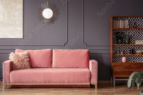 Simple, pink sofa with a fur pillow next to a wooden cupboard in ...