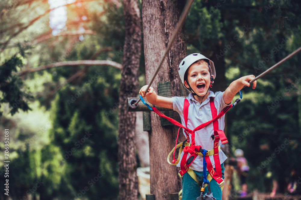 Fototapeta Little boy climbing in adventure activity park with helmet and safety equipment