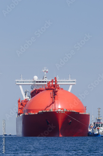 LNG TANKER - A big red ship with tugs