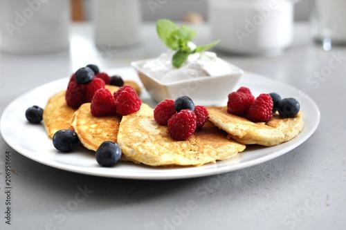 Placuszki z malinami i jagodami. Porcja smakowitych placuszków udekorowanych owocami malin i borówek, podanych z sosem jogurtowym