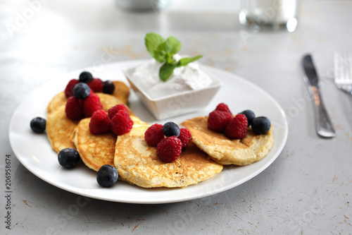 Fototapeta Śniadanie.   Porcja smakowitych placuszków udekorowanych owocami malin i borówek, podanych z sosem jogurtowym obraz