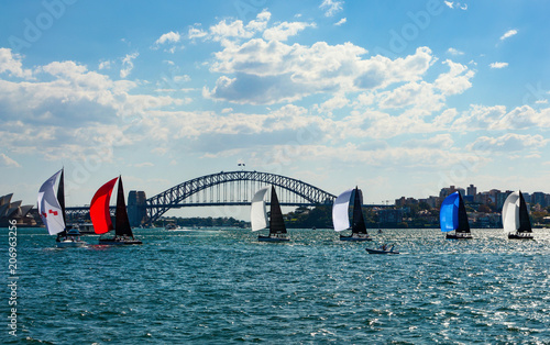 Colorful sailboats with spinnakers crossing Sydney Harbor in front of the iconic bridge in the background