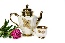 A White Teapot With A Golden F...