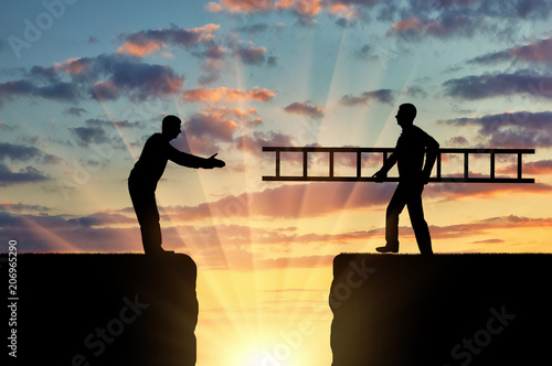 Photo A silhouette of a man carries a ladder to another man who is on the other side o