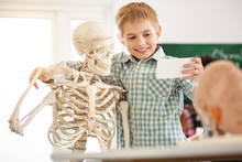My Friend. Happy Cute Boy Hugging A Skeleton While Taking A Selfie With Him