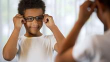 Happy Little Kid Trying On Eyeglasses, Looking In Mirror Satisfied Good Eyesight