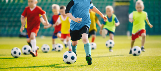 Football soccer training for kids. Children football training session. Kids running and kicking soccer balls. Young boys improving soccer skills
