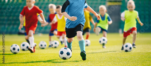 plakat Football soccer training for kids. Children football training session. Kids running and kicking soccer balls. Young boys improving soccer skills