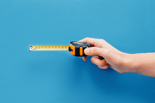 Bricolage Concept.Hand Holding Tape Measure On Blue Background