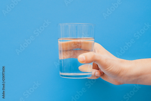 Drinking water concept one hand holding glass Canvas Print