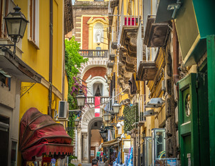 Narrow alley with Duomo steeple on the background in Sorrento