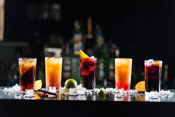 Višebojni alkoholni kokteli s limunima u čašama različitih oblika na šanku.