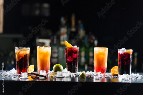 Valokuva Multi-colored alcoholic cocktails with citrus in glasses of different shapes on the bar
