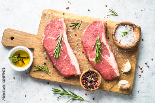 Raw beef striploin steak on cutting board. Canvas Print