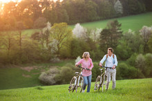 Beautiful Senior Couple With Bicycles Outside In Spring Nature.