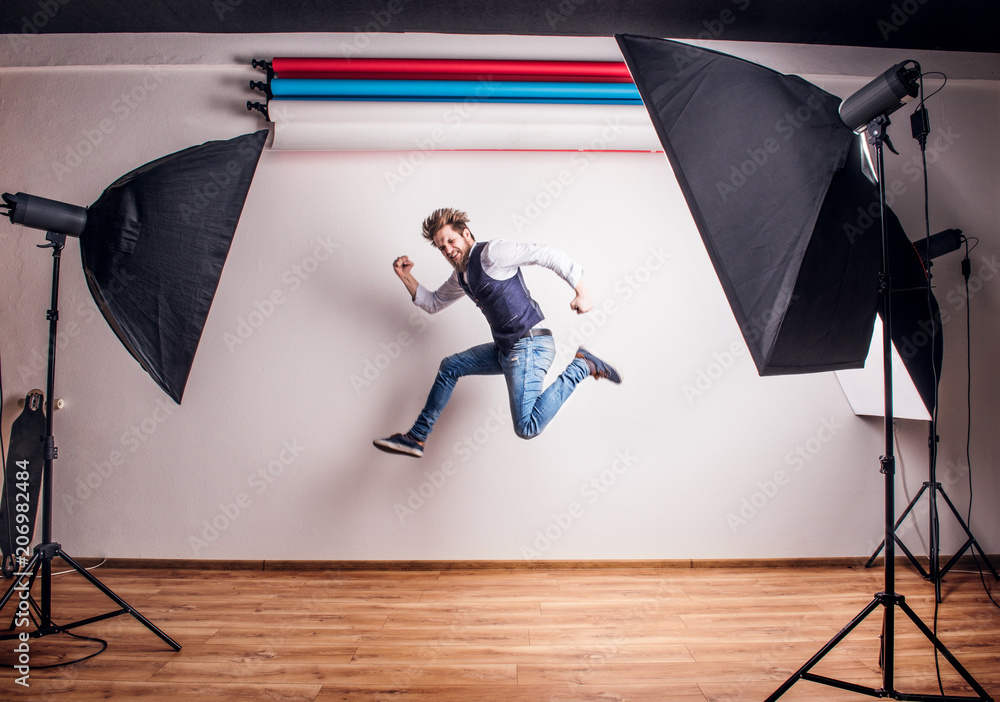 Fototapety, obrazy: Portrait of a young hipster man in a studio, jumping. Copy space.