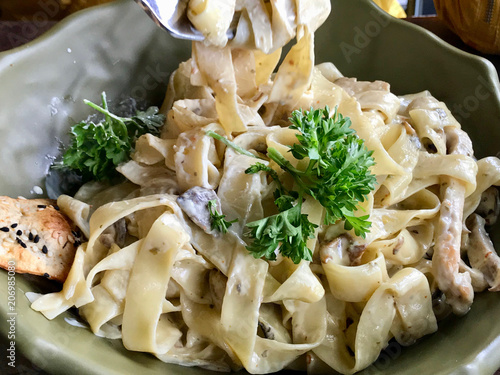 Photo Fettuccine Alfredo Pasta Dish with Cream, Chicken and Parsley served at Restaurant