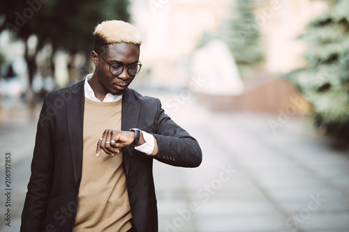 Fotografía  Handsome Afro American man looking at watch wearing suit in modern city street