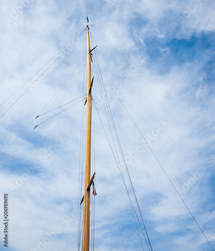 Poster Oceanië Ship mast with French flag against blue sky with white clouds. Travel background.