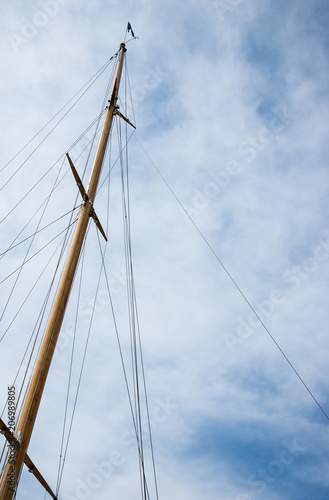 Poster Oceanië Ship mast with flag against blue sky with white clouds. Travel background.