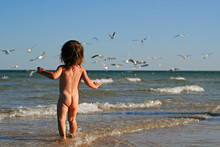 Naked Baby Standing In Water On A Background Of Sea And Seagulls