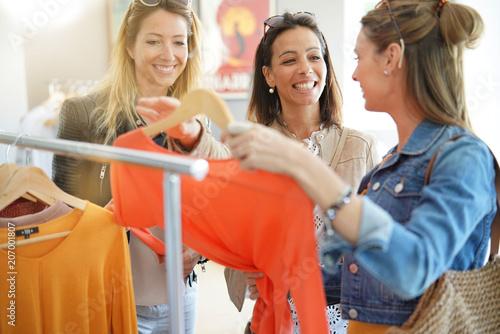 Photo  Girlfriends having fun shopping at clothing store