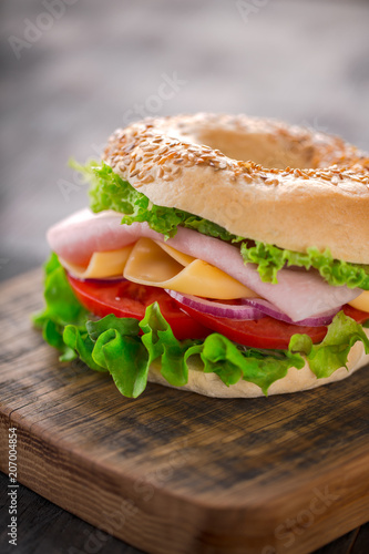 Deurstickers Snack Sesame bagel sandwich with lettuce, tomato, yellow cheese and ham.