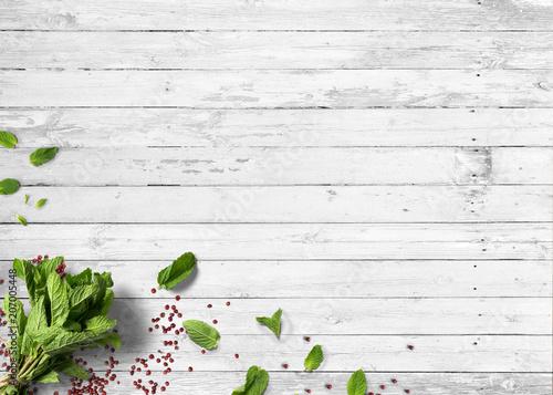 Bund frischer Kräuter mit Pfefferkörnern auf rustikalem Holztisch
