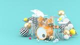 Orange drum amidst colorful balls on a blue background. - 3d render.