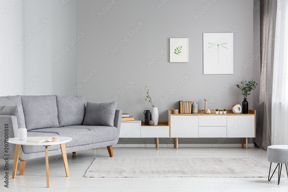 Fototapeta Grey settee near white cupboard in minimal living room interior with posters on the wall. Real photo