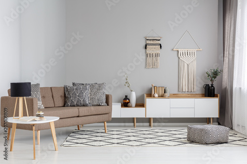 Foto op Canvas Restaurant Patterned pouf on carpet near brown sofa in modern living room interior with lamp on table. Real photo