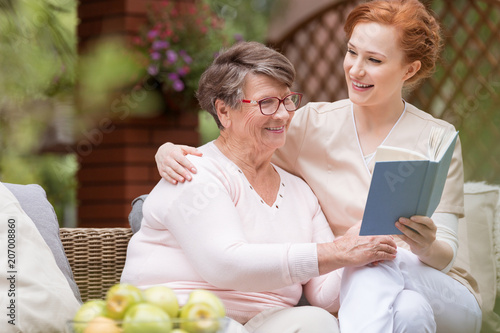 Photo  Cheerful senior woman with her tender caretaker reading a book together while relaxing outside