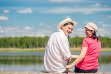 Happy Couple With A Fishing Rod Sitting On A Wooden Pier Near The Lake