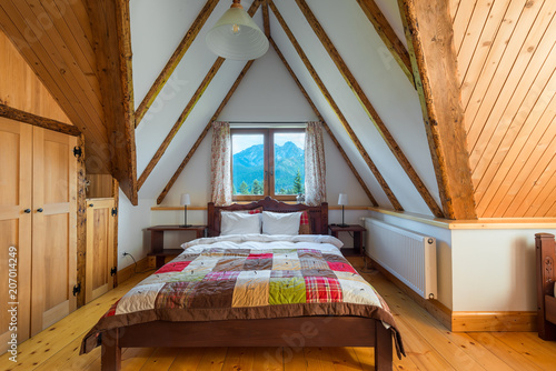 bedroom interior in a wooden house with a beautiful view from the window to the mountains