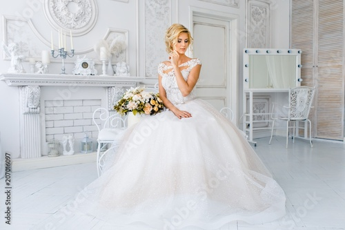 Fotografía A bride with hairstyle and make up in gougeous wedding dress preparing for the wedding