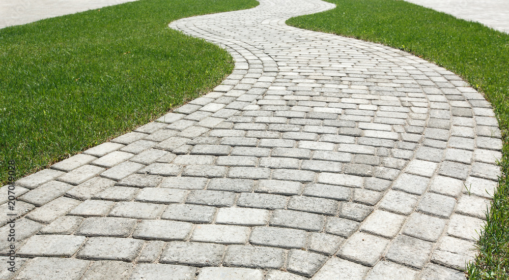 Fototapety, obrazy: Curved path in the shape of a wave on the grass in the Park. Paved with tiles of different shapes.