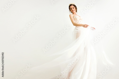 Fotografie, Obraz  young smily brunette sexy girl in a white wedding boudoir dress and crown in hai