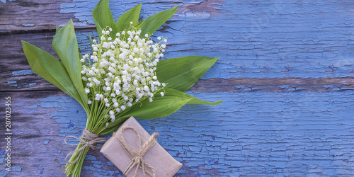 Staande foto Lelietje van dalen Bouquet of lilies of the valley and hand made gift box on old paint blue background with copy space