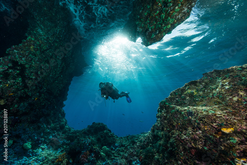 Tablou Canvas woman diver underwater at the entrance of a cave with sunrays