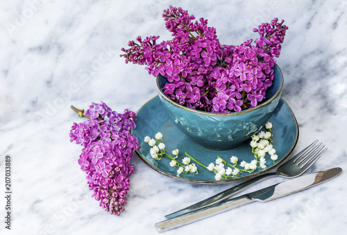 Fotobehang Lilac Spring Table Setting with Vintage Blue Cutlery and Lilac Flowers on a Marble Background.Floral Table Decor