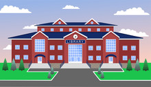 Library, Classic Brick Two-storey Building Of Red Brick And With A Blue Tiled Roof, With Three Entrances And A Clock In The Center, Against The Blue Sky, With Lawn, Paths, Firs