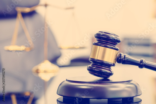 Fotografie, Obraz  Legal office of lawyers, justice and law concept : Wooden judge gavel or a wood hammer and a soundboard used by a judge person on a desk in a courtroom with a blurred brass scale of justice behind