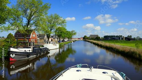 Fotografía  Hausboot fährt auf romantischem Kanal  entlang spiegelnden Häusern und Schiffen