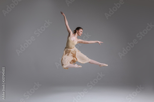 Fotografie, Obraz  Show yourself! Beautiful good-looking gorgeous ballerina showing classic ballet poses and jumping into the air on the grey background