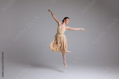 As light as a feather! Young attractive graceful gentle ballerina dancing in the art performance on the isolated background Fototapet