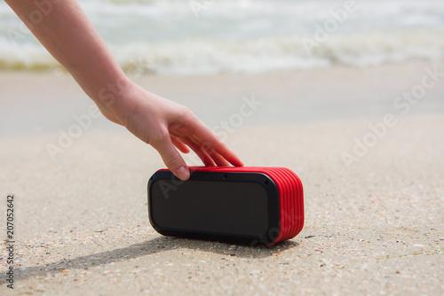 Obraz Female hand touch portable speaker - fototapety do salonu
